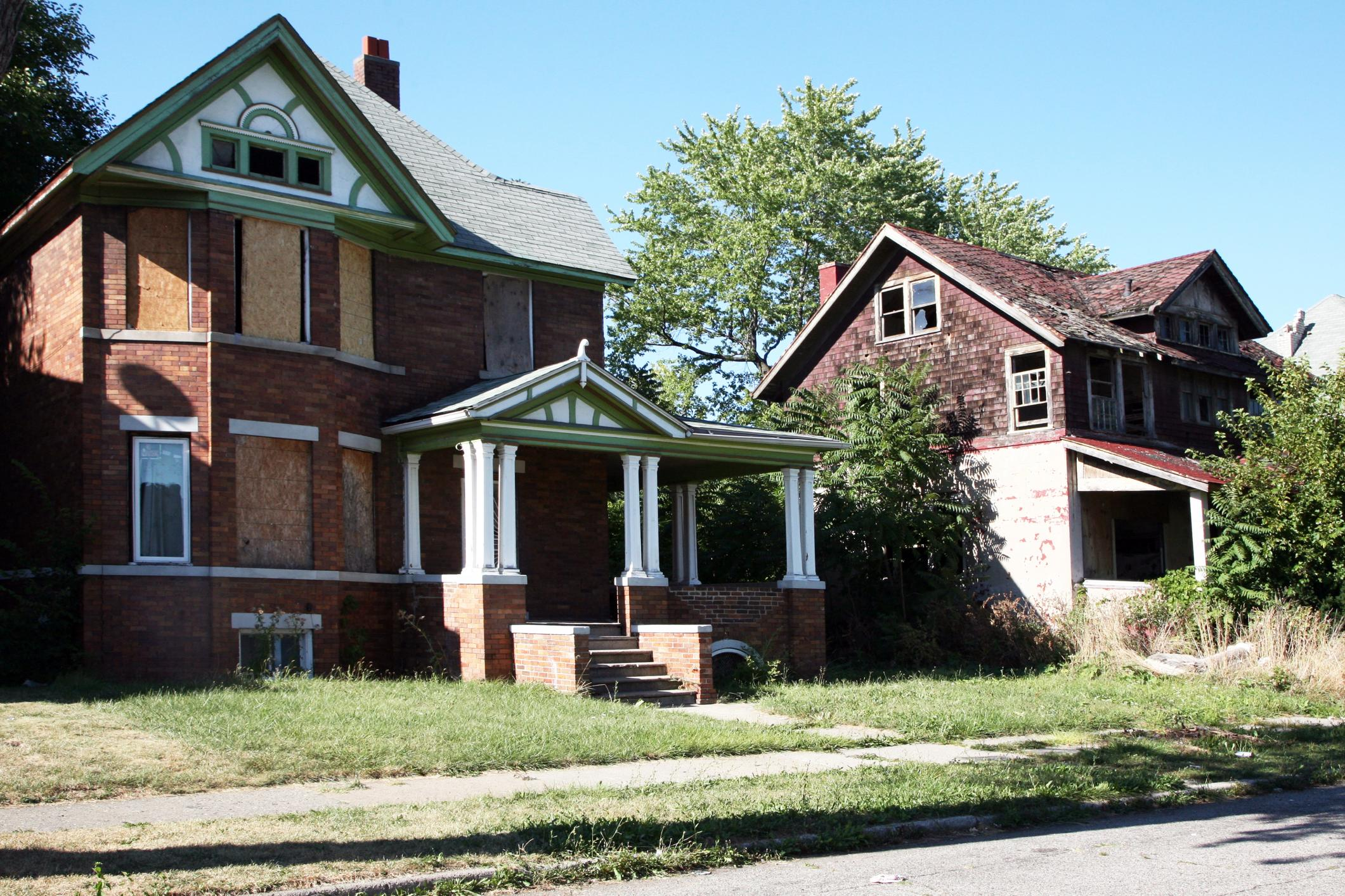 real estate iBuyer distressed house, with weeds and boarded up windows