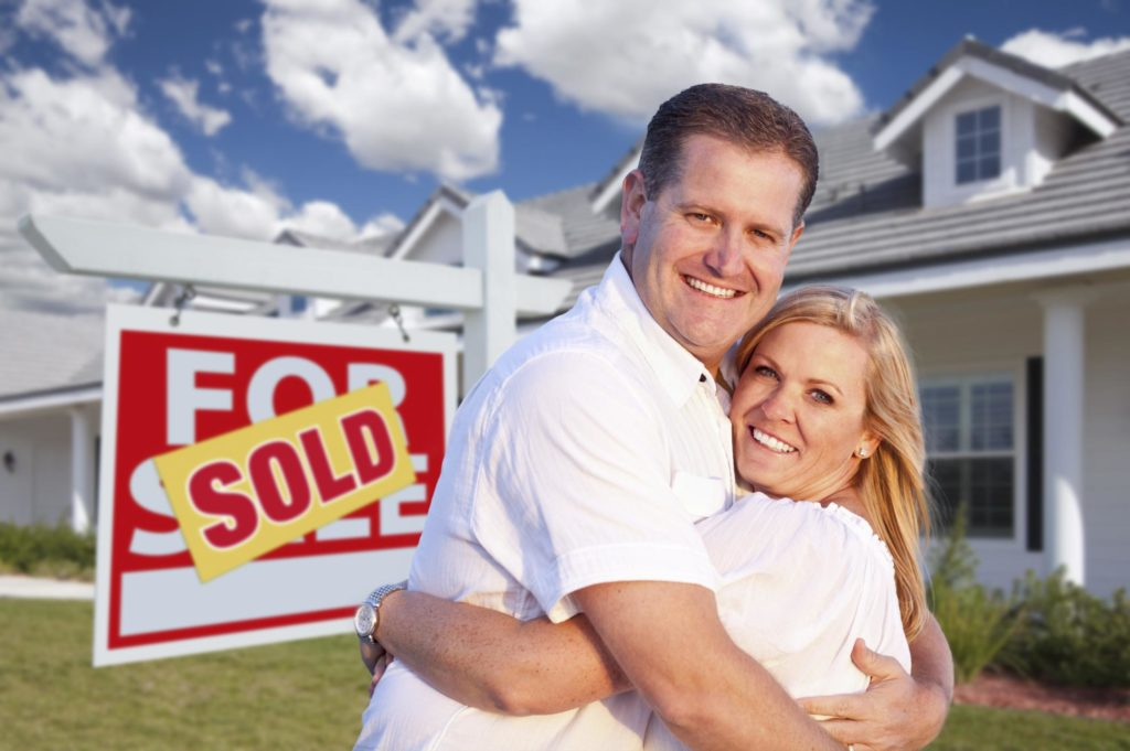 happy couple outside their sold house